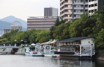世界遺産・原爆ドーム(左奥)近くで営業する「かき船」(手前右)=2018年9月、広島市