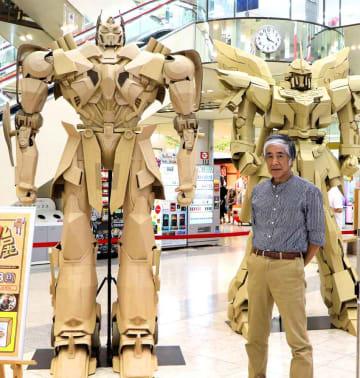映画製作会社の依頼で段ボールで再現した「トランスフォーマー」のキャラクター(左)と千田さん(京都府京丹後市峰山町・ショッピングセンター「マイン」)
