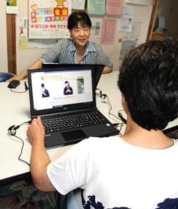 オンライン相談の開始に向けて打ち合わせをするボランティアスタッフ
