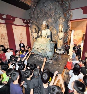 最先端技術と職人技で復元した奈良・法隆寺の国宝「釈迦三尊像」のスーパークローンに優しく触れる子どもたち=7月12日、福井県福井市の県立美術館
