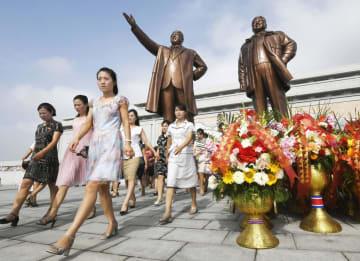 朝鮮戦争の休戦協定締結から66年を迎え、故金日成主席(奥左)と故金正日総書記の銅像が立つ「万寿台の丘」に献花に訪れた市民ら=27日、平壌(共同)