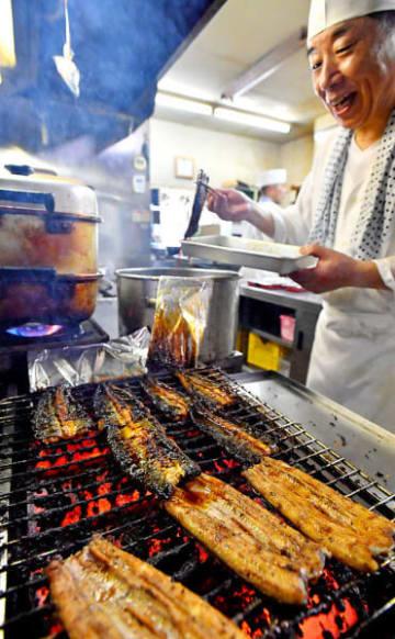 香ばしい匂いを漂わせ、伝統のたれで焼き上げられるウナギ=26日、盛岡市南大通・かわ広