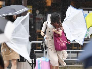 台風6号の接近で風雨が強まり、傘をあおられる歩行者=27日午前10時11分、名古屋市