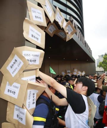 ソウルの日本大使館が入るビルの壁に抗議書簡を貼り付ける市民団体メンバー=27日(聯合=共同)