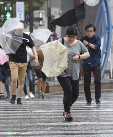 風雨が強まり、傘をあおられる歩行者=27日午後3時58分、名古屋市