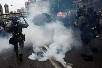 27日、香港の元朗で、抗議行動の参加者に向けて警官隊が発射した催涙弾の煙(ロイター=共同)
