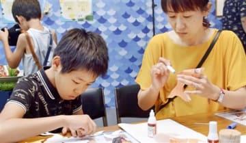 自分の顔写真が印刷された金魚のペーパークラフトを組み立てる親子=7月27日、福井県福井市の福井県立美術館