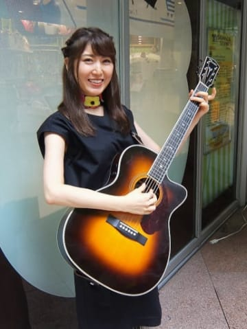 愛用のギターを抱えて歌う流し出身のおかゆ=大阪市内