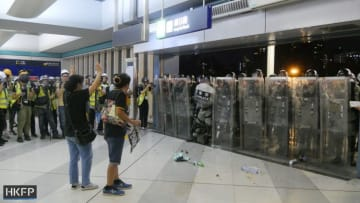 Lui Yuk-lin and another protester urge riot police not to enter Yuen Long MTR station. Photo: Holmes Chan/HKFP.
