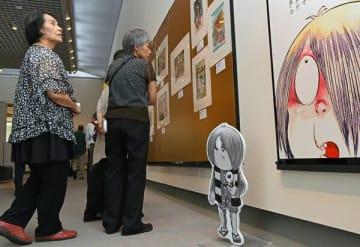 代表作である「ゲゲゲの鬼太郎」の漫画原稿などに見入る来場者=27日午後、宇都宮美術館
