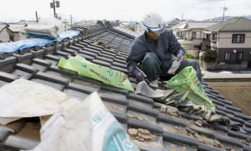 突風で損壊した屋根を補修する作業員=27日午後、栃木県佐野市