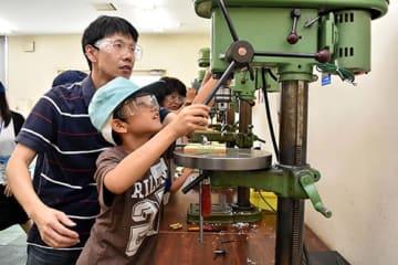 機械を使ってアクリル板に穴を開ける参加者=山形市・ポリテクセンター山形