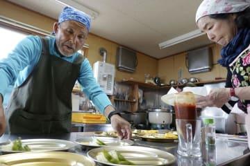 薬師岳山荘で食事の準備をする川原修さん(左)と堀井よし子さん=7日、富山市