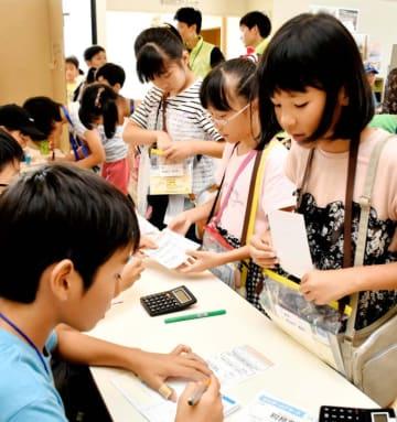 子どもだけで運営する仮想の町の税務署で納税をする小学生(右)=27日午後、新居浜市高木町