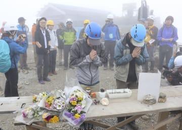 御嶽山の山頂付近で噴火犠牲者を追悼する遺族ら=28日