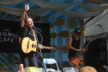 フジロックフェスティバルの「アトミック・カフェ」で歌を披露し、歓声に応える玉城デニー知事(左)=28日、新潟県湯沢町の苗場スキー場
