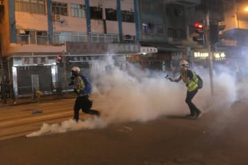 Journalist walk next to a police fire tear gas canister during a demonstration against what activists say is police violence in Hong Kong on July 28, 2019. Photo: Vivek Prakash/AFP.