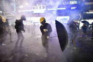 Protesters are enveloped by tear gas let off by police during a demonstration against a controversial extradition bill in Hong Kong on July 28, 2019. Photo: Anthony Wallace/AFP.