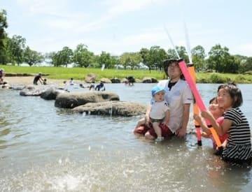 強い日差しの下、鴨川河畔公園で水遊びをする子どもたち=28日午後、菊池市