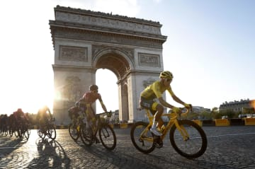 ツール・ド・フランス最終ステージ、総合優勝へ向け、凱旋門前を駆け抜けるエガン・ベルナル=28日、パリ(AP=共同)