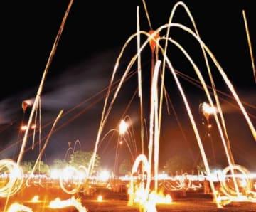メイン行事の「柱松」。投げ込まれたたいまつの光跡が夜空を照らす=28日夜、大分市の七瀬川自然公園