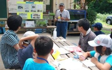 【鈴鹿川に生息する魚について講義する浅田代表(中央)=亀山市椿世町の里山公園「みちくさ」で】