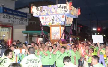 元気を届けたいと掛け声を上げ神輿を担ぐメンバー=28日夜、久喜市の鷲宮神社通り