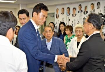 落選を報告後、支援者と握手をする中田宏氏=22日午前5時50分ごろ、東京都内の事務所