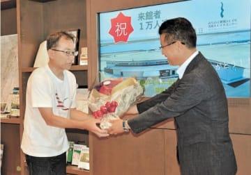 入館1万人目となり、花束を受け取る荒井さん(左)