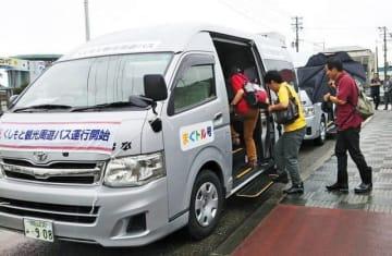 観光周遊バス「まぐトル号」に乗り込む観光客ら(和歌山県串本町串本で)