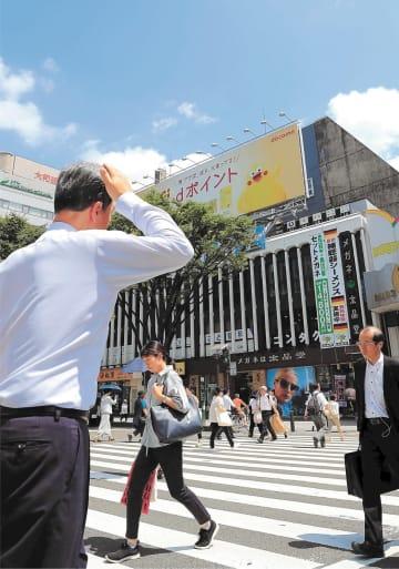 強い日差しが降り注ぐ中、汗を拭う会社員=29日午前10時35分ごろ、仙台市青葉区中央2丁目