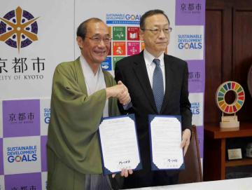 連携協定を締結し、握手を交わす太田理事長(右)と門川市長=京都市中京区・市役所