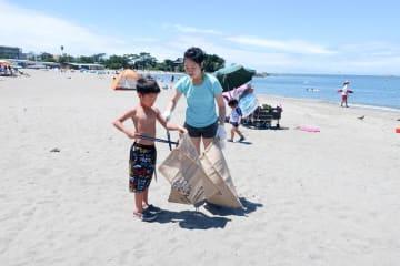海岸清掃に取り組む海水浴客=森戸海水浴場