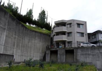 古田中のコンクリート擁壁のそばに立つ男性のアパート。敷地の一部に市有地が含まれている(広島市西区)