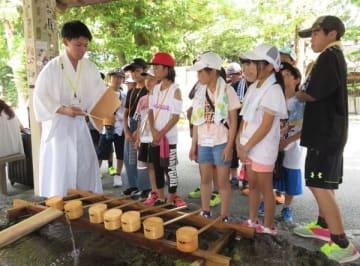 【神職から手水の作法を学ぶ子どもたち=伊勢市の猿田彦神社で】