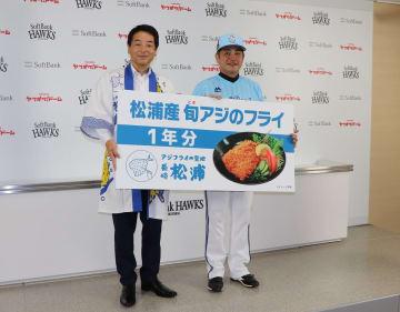 工藤監督(右)にアジフライを贈った友田市長=福岡市、ヤフオクドーム