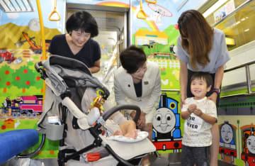 都営地下鉄大江戸線車内の子育て応援スペースで親子に話しかける小池百合子都知事(中央)=30日午前