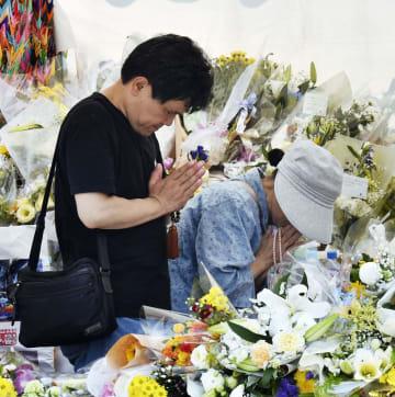 事件現場近くの献花台で手を合わせる人たち=30日午後、京都市伏見区