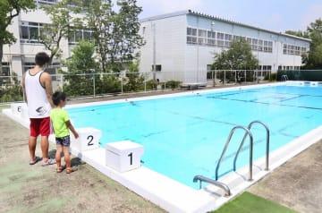 プール開放中止を知らずに訪れ、入れないプールを見つめる親子=7月29日、福井県福井市木田小学校