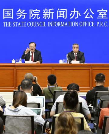 記者会見する中国新疆ウイグル自治区のショハラト・ザキル主席(左)とエルキン・トゥニヤズ副主席=30日、北京(共同)