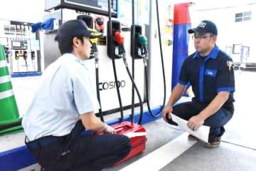 ガソリンスタンドの従業員に携行缶での購入について注意喚起する宮崎市消防局の職員=30日午後、宮崎市