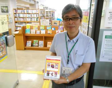 個人の端末で利用できる電子図書館サービスをPRする稲垣館長=綾瀬市立図書館、2019年7月26日撮影