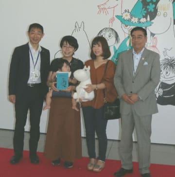 「ムーミン展」で2万人目の入場者になった安見千鶴ちゃんと母親の万智さん(左から2人目)、野々下菜々子さん(同3人目)=30日、大分市の県立美術館
