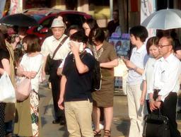 強い日差しが照り付け、タオルで汗をぬぐう人=30日午後、神戸市中央区元町通1(撮影・後藤亮平)