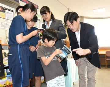 寄贈した本を子どもたちに紹介する本間希樹所長(右)と田崎文得特任研究員(右から2人目)