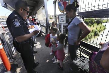 メキシコ北東部ヌエボラレドの国境で、移民の書類を確認する米税関・国境警備局の職員=7月17日(AP=共同)