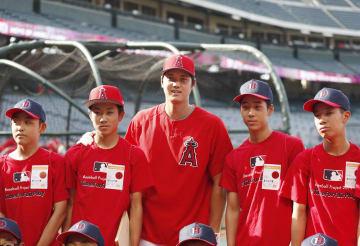 試合前、球場を訪れた宮城、熊本両県の中学生と記念撮影するエンゼルス・大谷(中央)=アナハイム(共同)