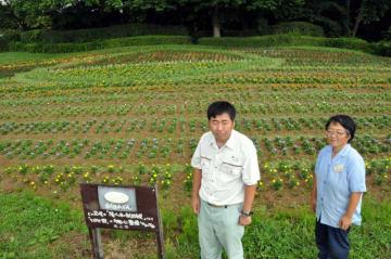 ラグビーボールをかたどった花壇の前で出来を喜ぶ及川悠行さん(左)と八重樫恵美子さん