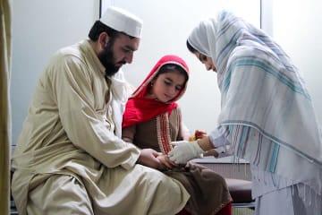 指を刺され治療に来たアフィアさんと父親 © Nasir Ghafoor/MSF