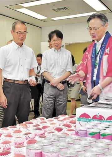 福島県産モモの説明を受けながら品定めする更田氏(左)